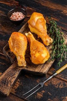 Маринованные и копченые куриные окорочка на деревянной разделочной доске на деревянном столе. вид сверху.