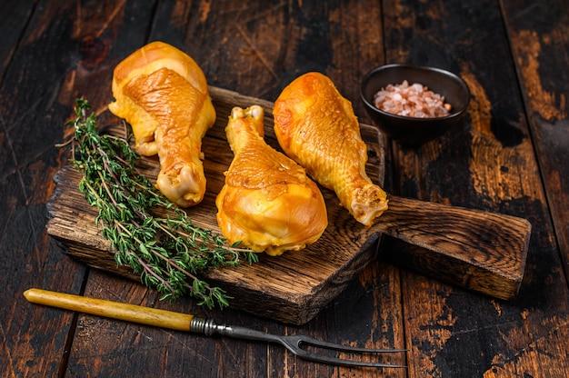 Голени куриные окорочка маринованные и копченые на деревянной разделочной доске.