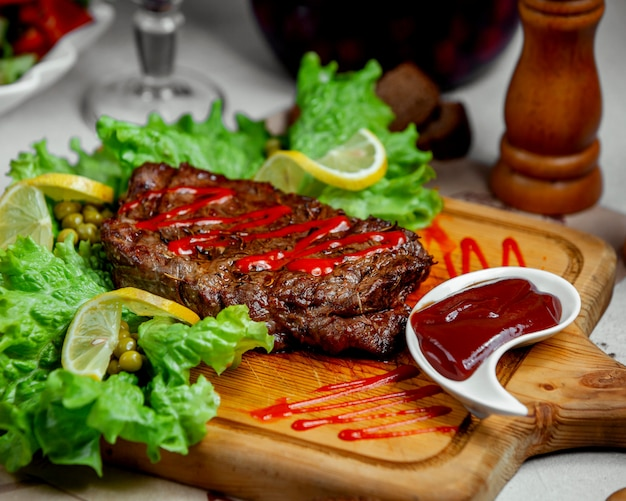 Marinated beef steak served with ketchup and lemon