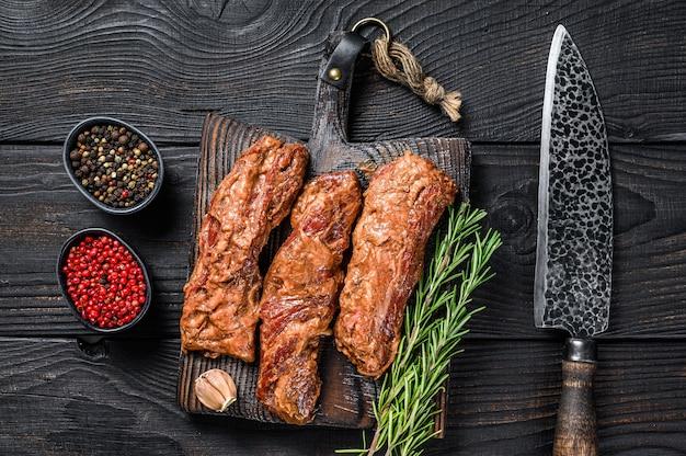 Маринованные стейки из грудинки в соусе барбекю на деревянной разделочной доске с травами на деревянном столе. вид сверху.