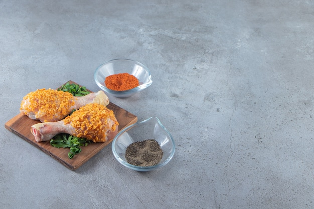 Coscia di pollo marinata su una vegetazione su una tavola, sullo sfondo di marmo.