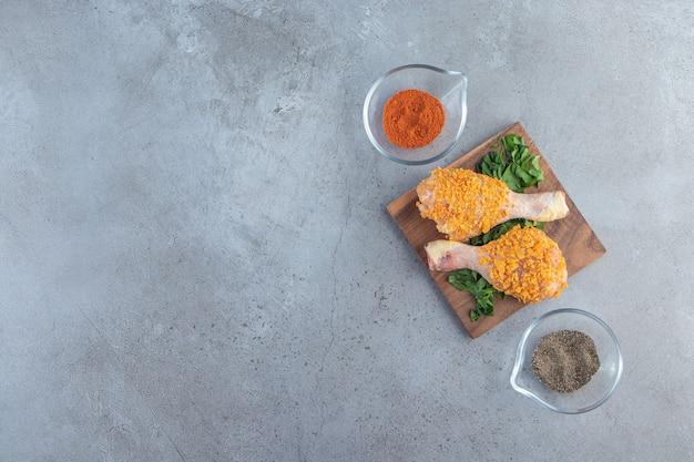 Coscia di pollo marinata su un verde su una tavola, sullo sfondo di marmo.