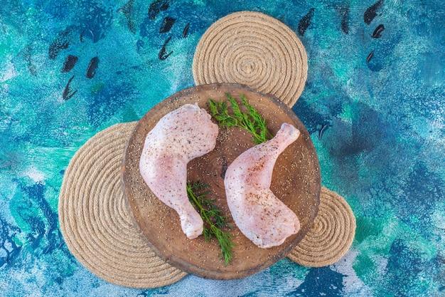 Coscia di pollo marinata con aneto su tavola su sottopentola