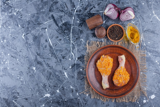 Marinated chicken drumsticks on a plate on a burlap next to spice and onion on the blue surface