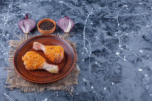 Marinated chicken drumsticks on a plate on a burlap next to spice and onion, on the blue table.
