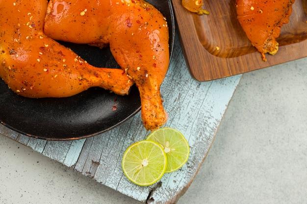 Маринованные куриные окорочка и филе грудки на раскрашенной разделочной доске.