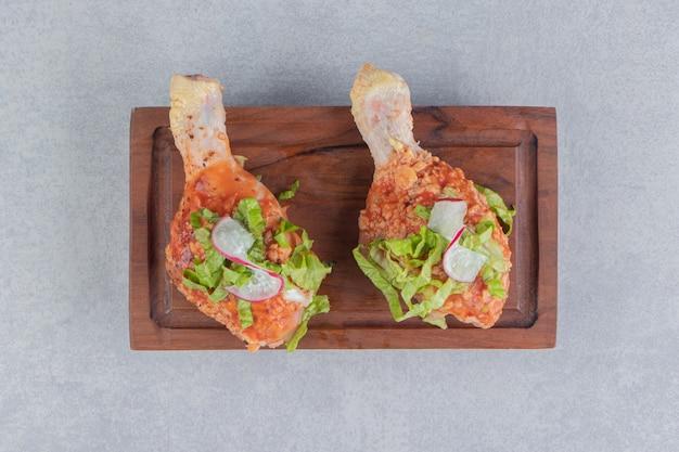 Cosce di pollo marinate sulla tavola, sulla superficie del marmo