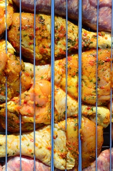 Marinated chicken legs on hot bbq charcoal field grill