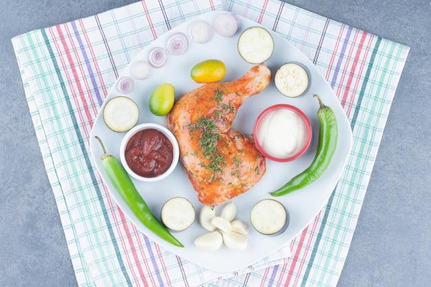 Маринованная курица на тарелке с нарезанными овощами.