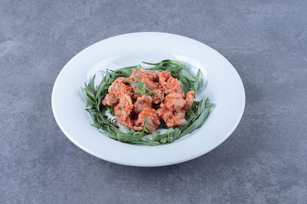 절인된 닭고기 조각과 하얀 접시에 타라곤입니다.