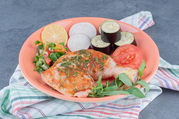 Pollo marinato e verdure affettate sulla zolla arancione.