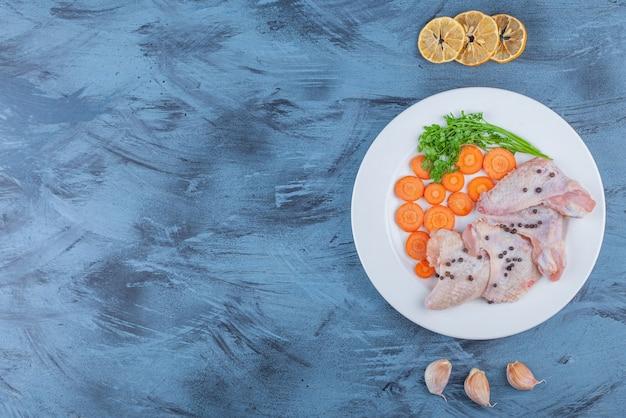 青い表面の皿に手羽先のマリネと様々な野菜