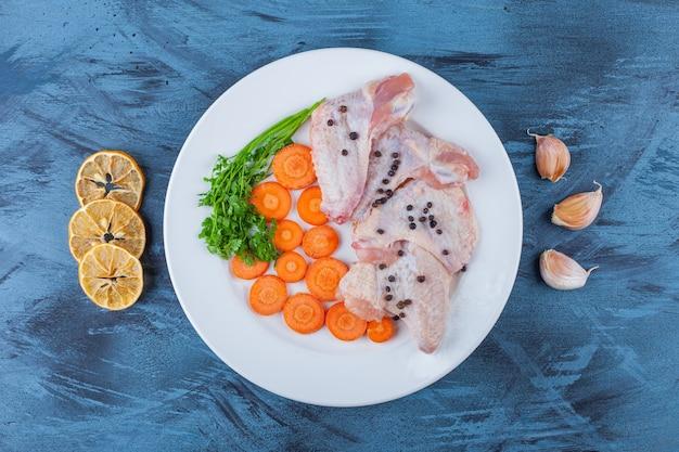 파란색 표면에 접시에 절인 닭 날개와 다양한 야채