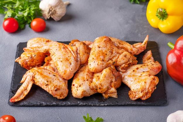 Куриные крылышки маринованные в красном соусе. сырые куриные крылышки готовы к приготовлению