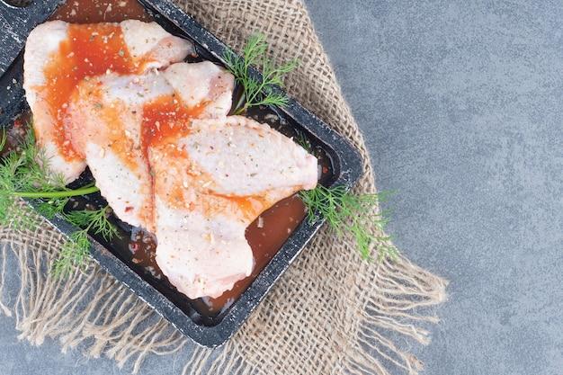 Ali di pollo marinate con salsa a bordo nero.