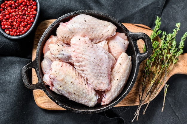 Маринованные куриные крылышки со специями и зеленью на сковороде.