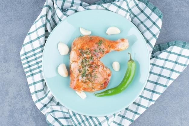 파란색 접시에 마늘과 후추와 절인 된 닭고기.