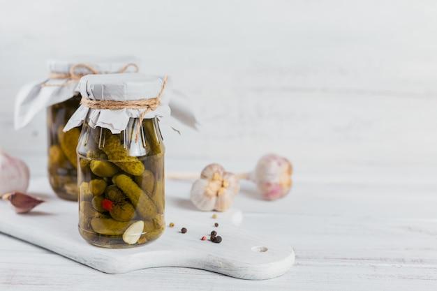 Маринованные огурцы корнишоны с укропом и чесноком в стеклянной банке на белом деревянном столе