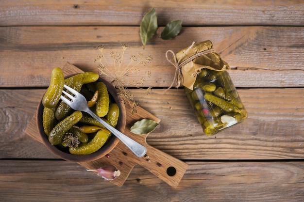 Маринованные огурцы-корнишоны с укропом и чесноком в стеклянной банке на деревянном столе
