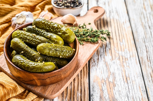 Marinated cucumbers gherkins in wooden plate