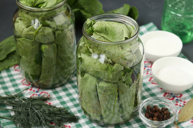 Premium Photo Marinated Cucumbers In Grape Leaves In Jars For The Winter With Garlic And Dill Preparatory Process Closeup