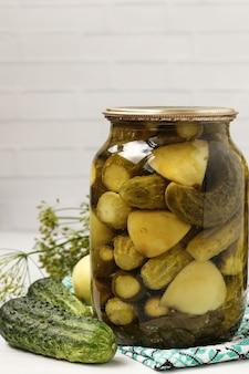 瓶にリンゴを入れたきゅうりのマリネは白い背景に配置されています、冬の収穫、クローズアップ、垂直写真