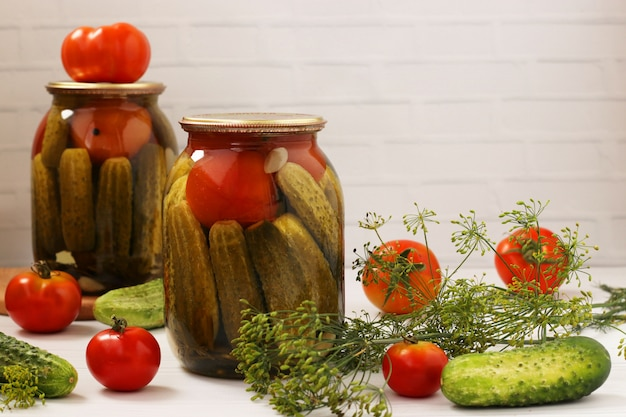 Marinated cucumbers with tomatoes are located in glass jars