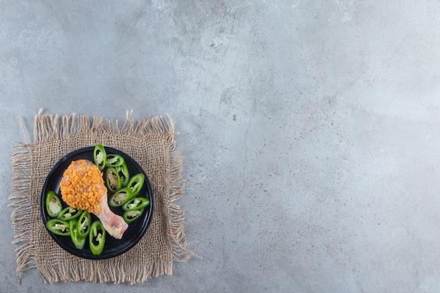 Маринованная голень и нарезанный перец на тарелке на салфетке из мешковины, на мраморном фоне.