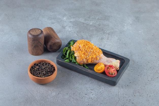 Bacchetta marinata su una tavola accanto alla ciotola delle spezie, sulla superficie di marmo.