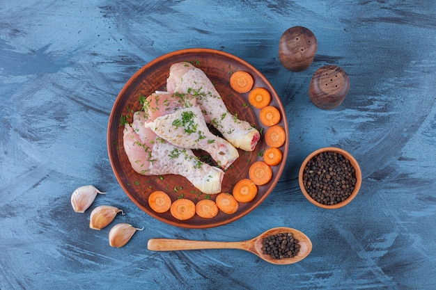 파란색에 향신료, 숟가락 및 마늘 옆 나무 접시에 절인 된 나지만 및 슬라이스 당근.