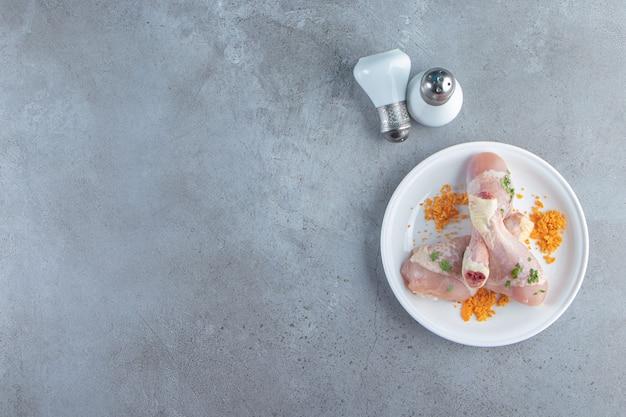 Маринованная свежая голень на тарелке рядом с солью, на мраморном фоне.