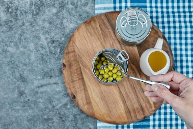 Fagiolini marinati nel barattolo metallico con olio d'oliva intorno.