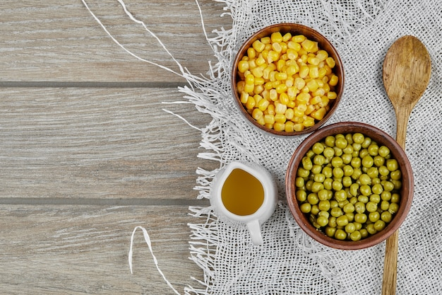Marinated green pea beans with corns in wooden cups.