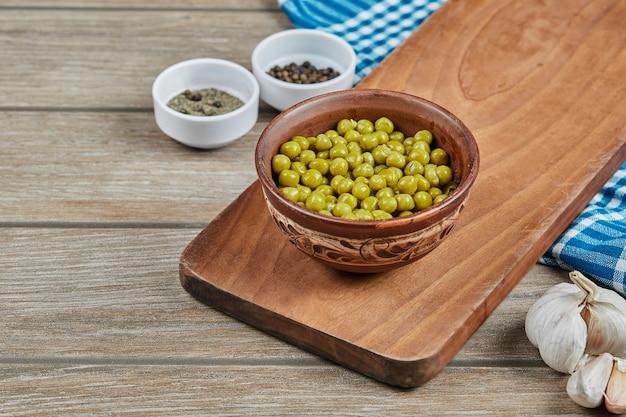 Fagioli verdi marinati in una tazza di legno.