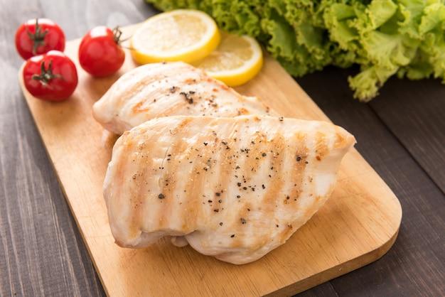 木製テーブルの上の鶏胸肉のグリルマリネ。