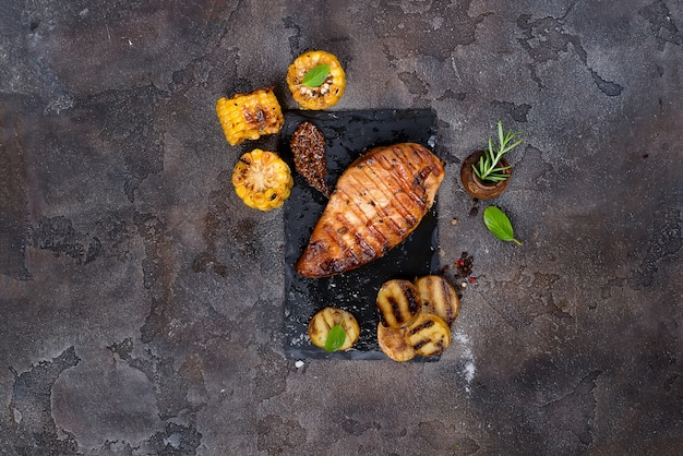 Marinated grilled healthy chicken breasts  and served with fresh herbs, potatoes and corn