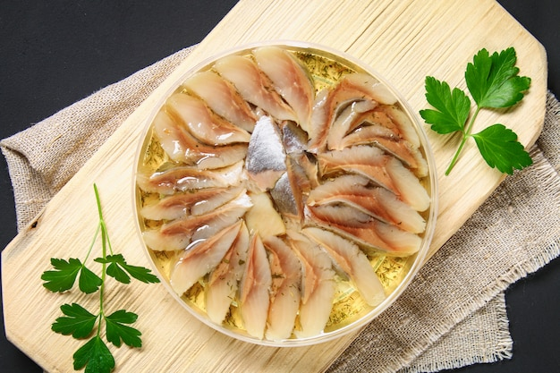 Marinated herring in oil on a wooden board
