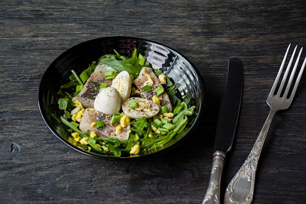 Marinated herring with arugula, onions, boiled quail eggs and lemon juice and olive oil.