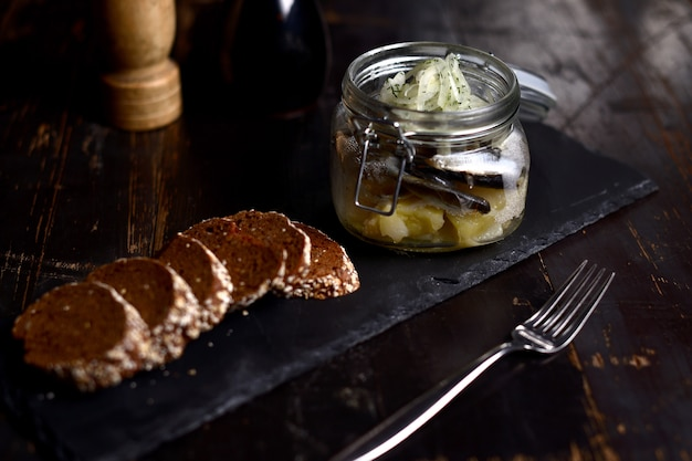 Marinated herring with onions in a glass jar, on a dark background