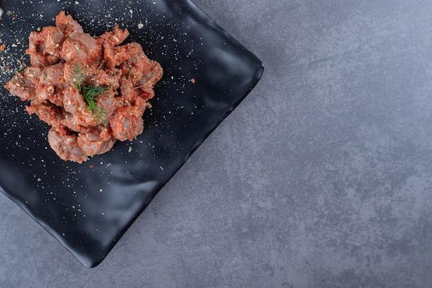 Кусочки маринованного шашлыка на черной тарелке.