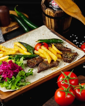 Marinated kebab served with french fries lettuce pickles grilled tomato and pepper