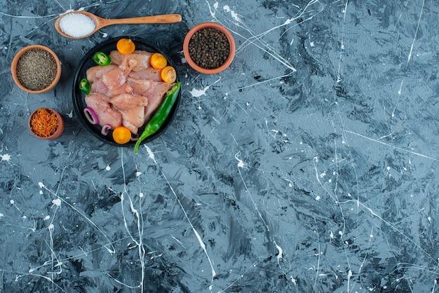青い表面のボウルとスプーンのスパイスの隣のプレートにマリネした肉と野菜