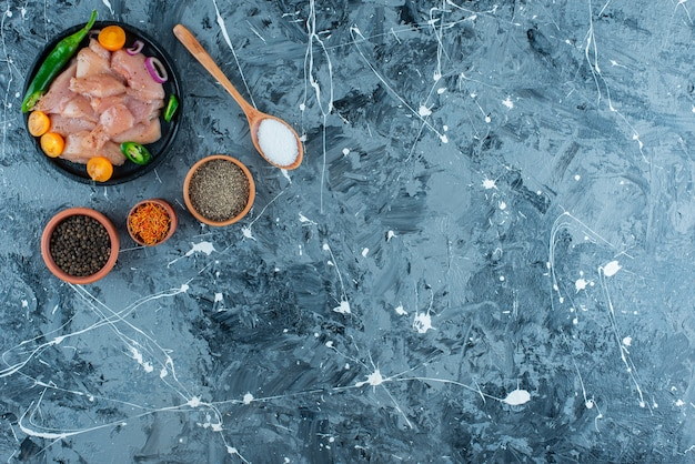 Carne e verdure marinate su un piatto accanto alle spezie in ciotole e cucchiaio sulla superficie blu
