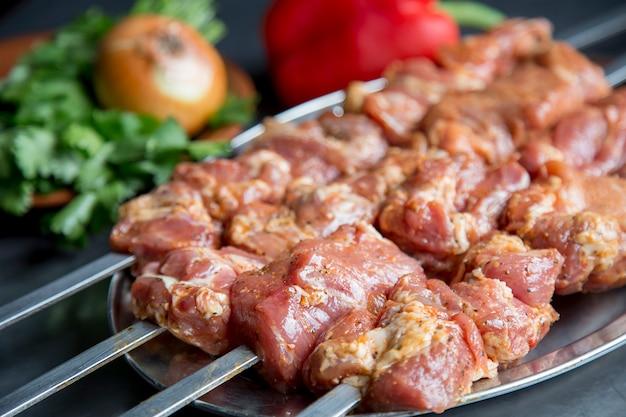 야채와 함께 절인 고기. 꼬치에 돼지 고기 sashlik