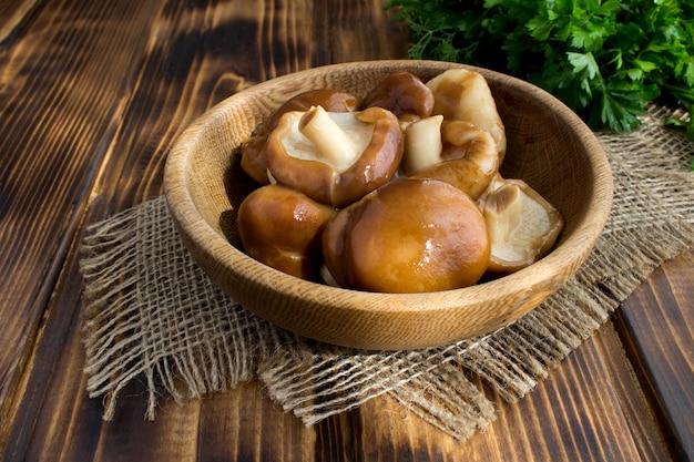 素朴な木製の背景に茶色のプレートでマリネしたキノコ椎茸