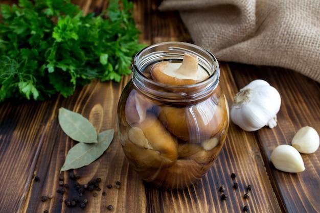 茶色の素朴な木製の表面にガラスの瓶にキノコのしいたけのマリネ
