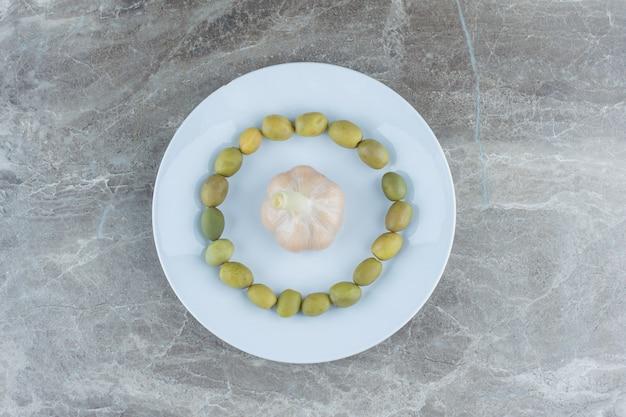 Маринованные оливки вокруг консервированного чеснока на белой тарелке.