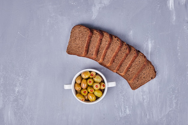 Marinated olives with black bread slices.