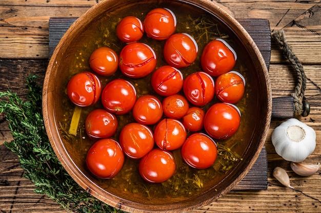 마늘과 백리향 나무 접시에 절인된 절인된 체리 토마토. 나무 배경입니다. 평면도.