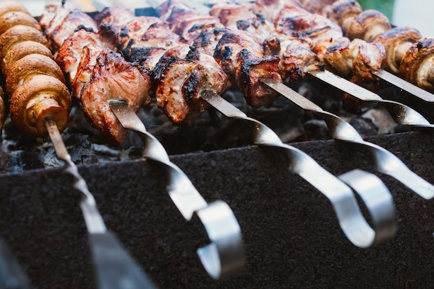 Marinated pieces of meat and mushrooms are grilled on charcoal s